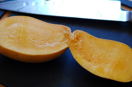 Slice lengthwise, along flat side of mango seed/pit